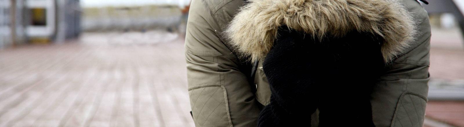 Verzweifelte Frau mit Kapuze über dem Kopf verdeckt das Gesicht hinter ihren Händen