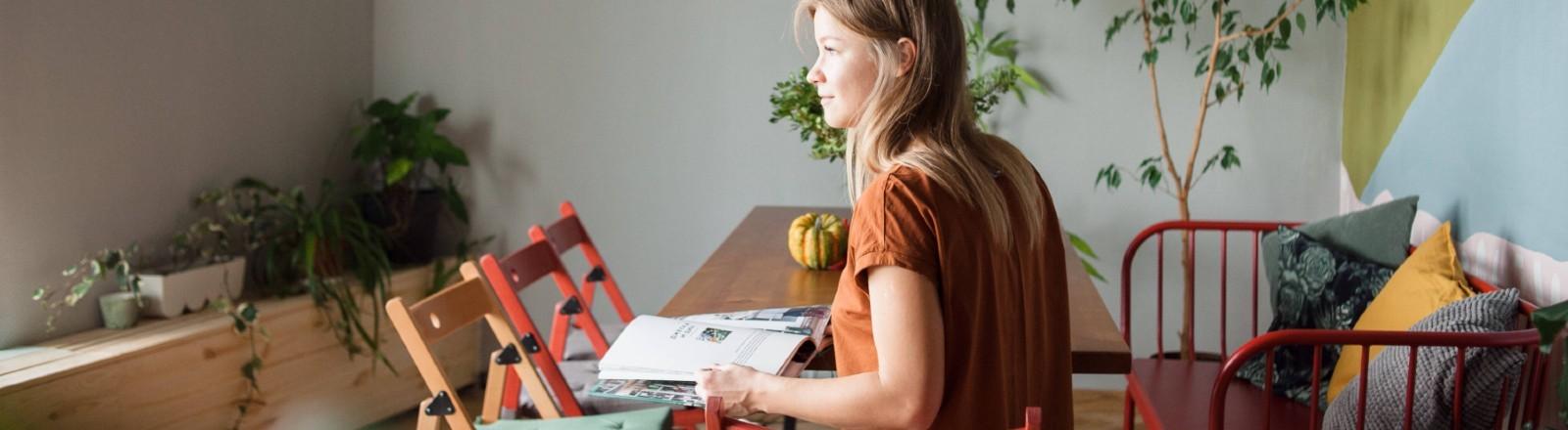 Frau sitz an einem Küchentisch, vor sich ein Magazin