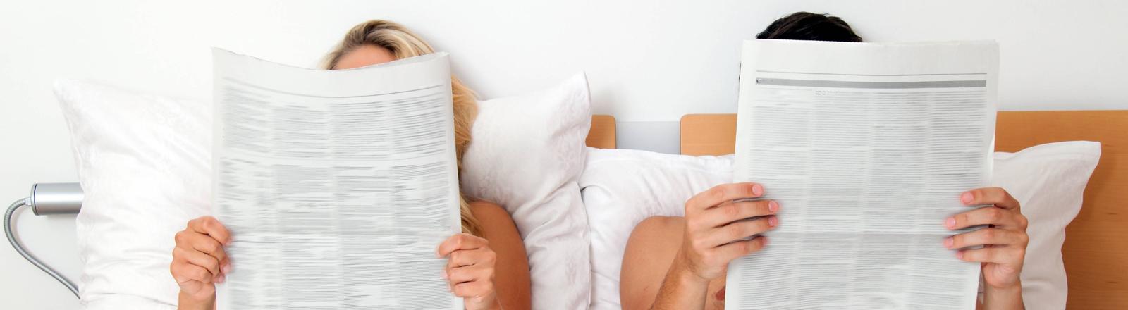 Zeitunglesendes Paar im Bett