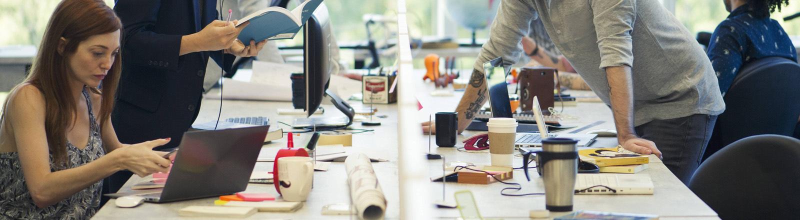 Bürogemeinschaft mit Menschen, die an einem langen Tisch sitzen und arbeiten.