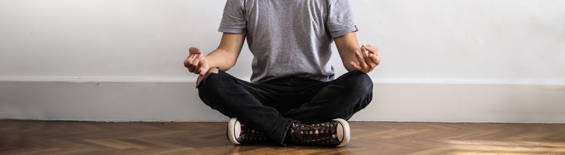 Mann in Jeans, T-Shirt und mit Turnschuhen, sitzt im Schneidersitz und meditiert.