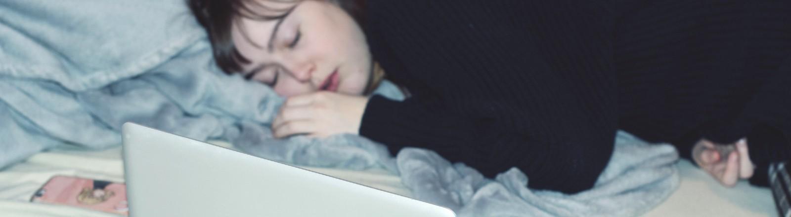 Frau liegt auf dem Bett und schläft. Neben ihr steht ein Laptop und daneben liegt eine Brille.