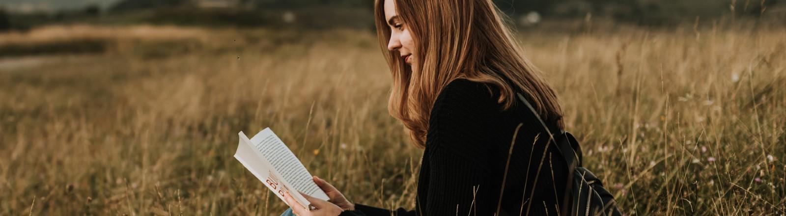 Eine junge Frau sitzt in der Natur mit einem Buch in der Hand.