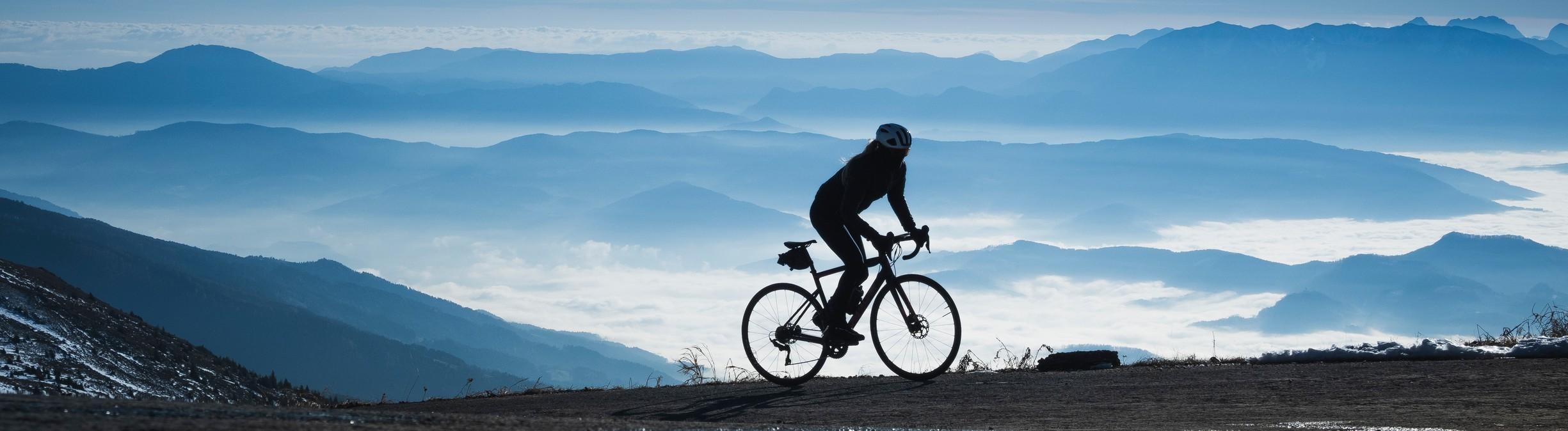 Fahrradfahrer auf Rennrad. Im Hintergrund Berge.