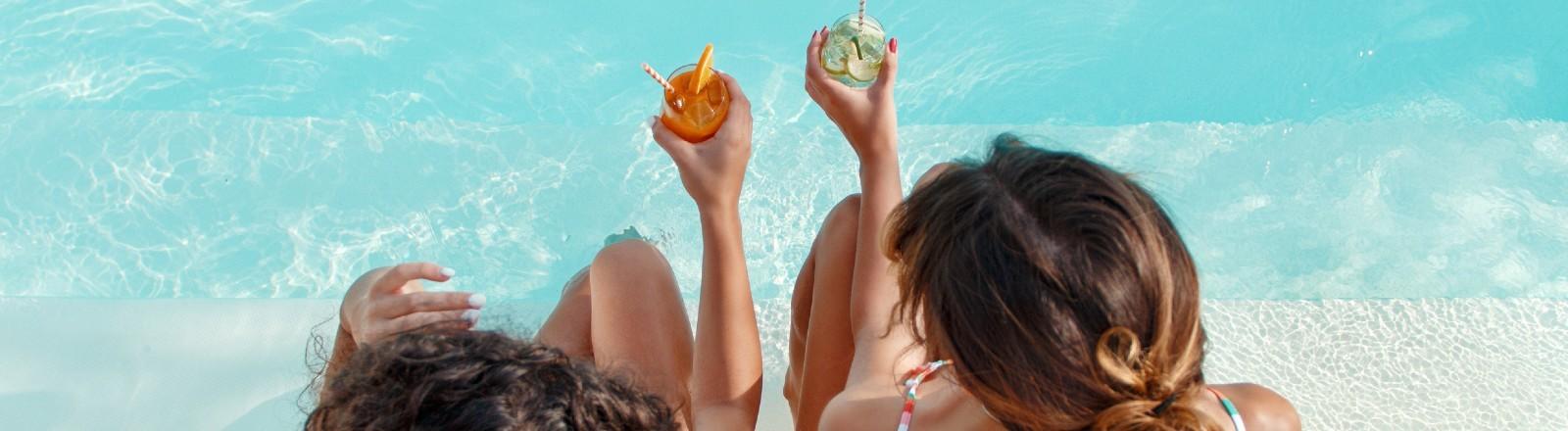 Zwei junge Frauen in Badeanzügen entspannen und trinken tropische Cocktails am Pool.