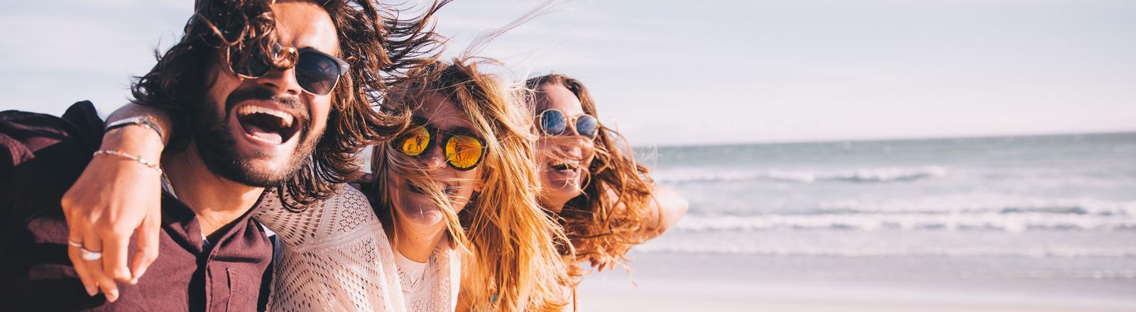 Drei Freunde am Strand: Mann, Frau, Frau