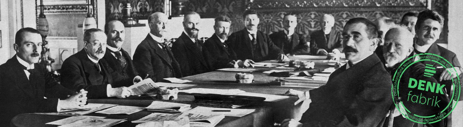Alte Aufnahme zeigt Männer, die um einen großen Tisch sitzen.