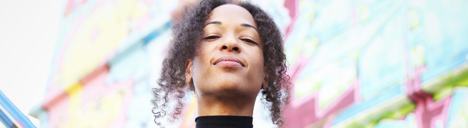 Ein junge Frau hält den Kopf oben und lächelt