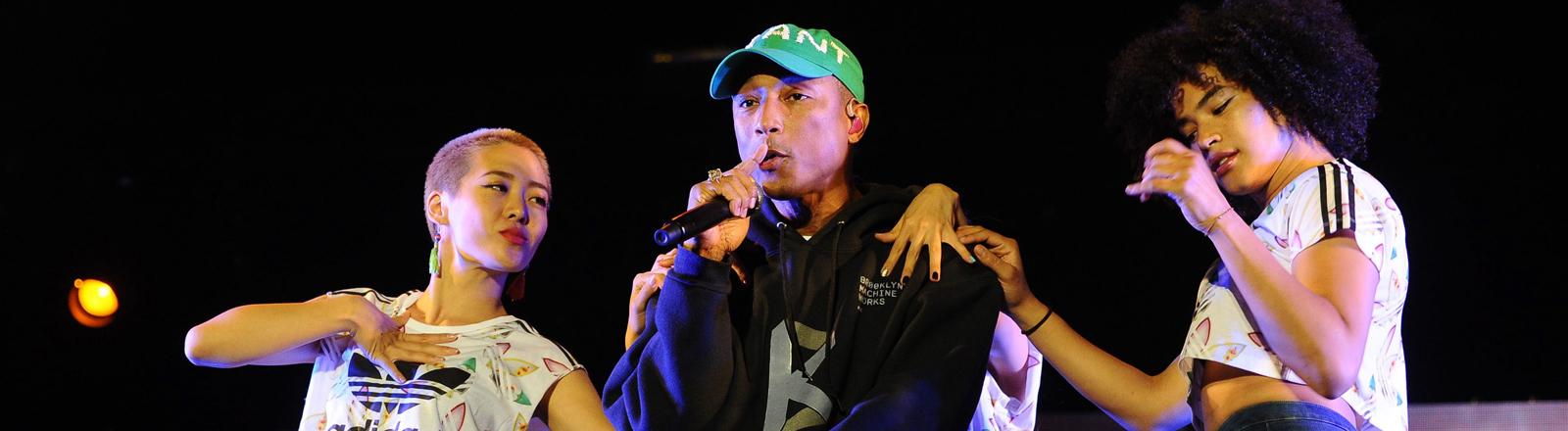 Pharrell Williams auf der Bühne mit Tänzerinnen.