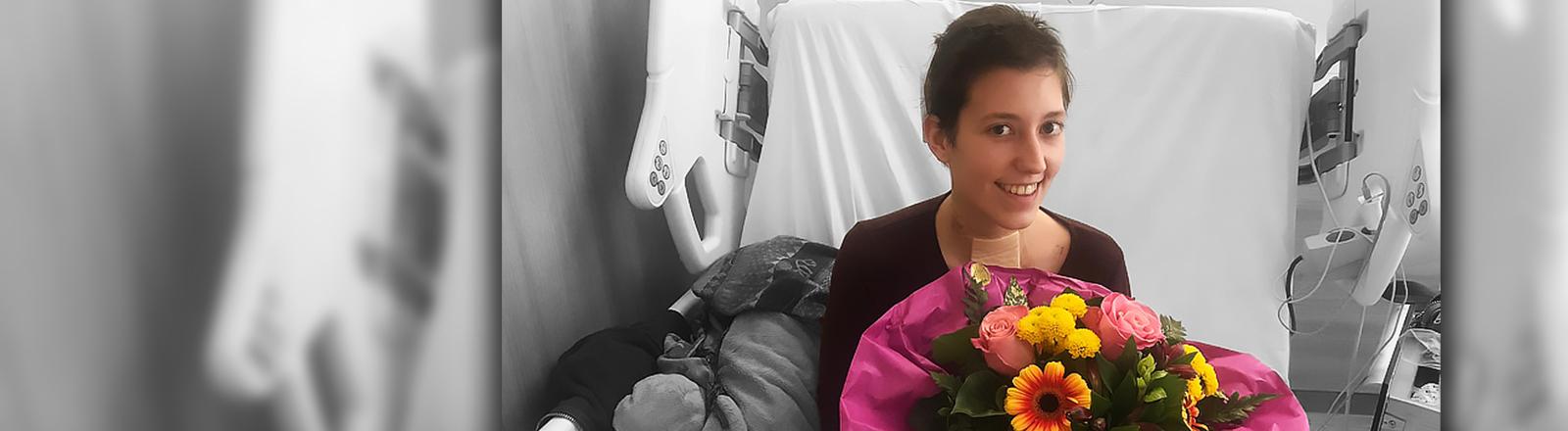 Luisa sitzt mit einem Blumenstrauß in ihrem Krankenbett