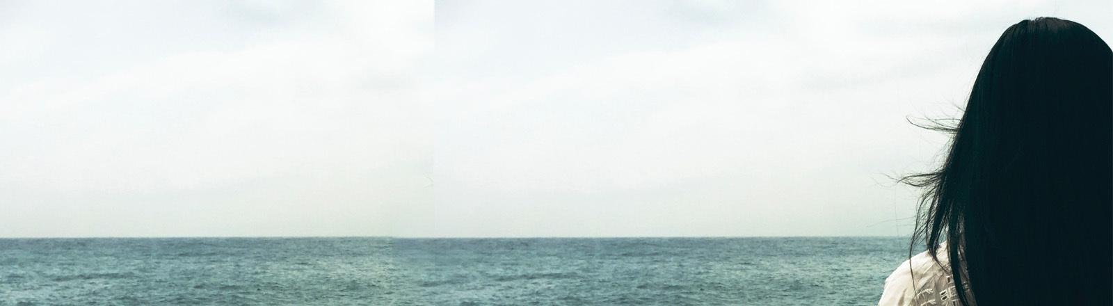Eine Frau steht alleine vor dem Meer
