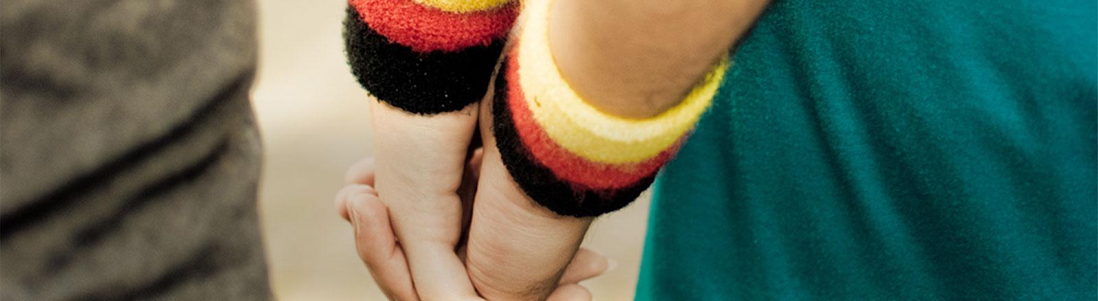 Zwei Menschen gehen Hand in Hand. Um ihre Handgelenke tragen sie Schweißbänder in den deutschen Farben.