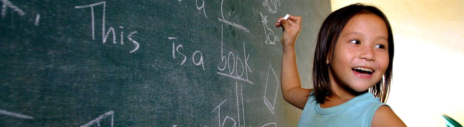 Ein Mädchen mit asiatischen Gesichtszügen steht an einer Tafel und schreibt englische Worte daran.