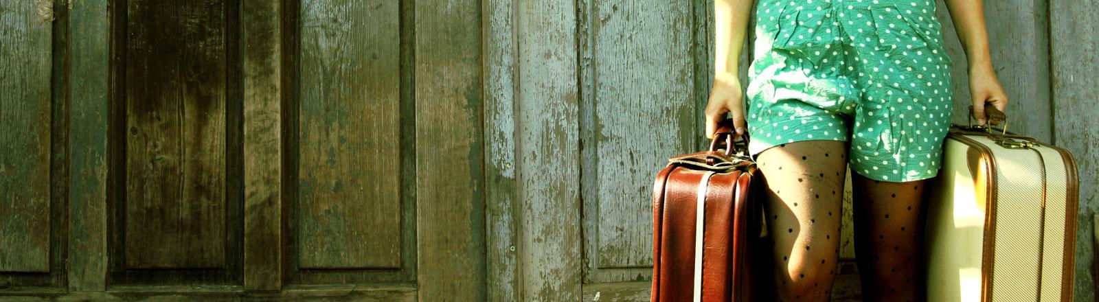 Eine Frau hält zwei Koffer in ihren Händen.