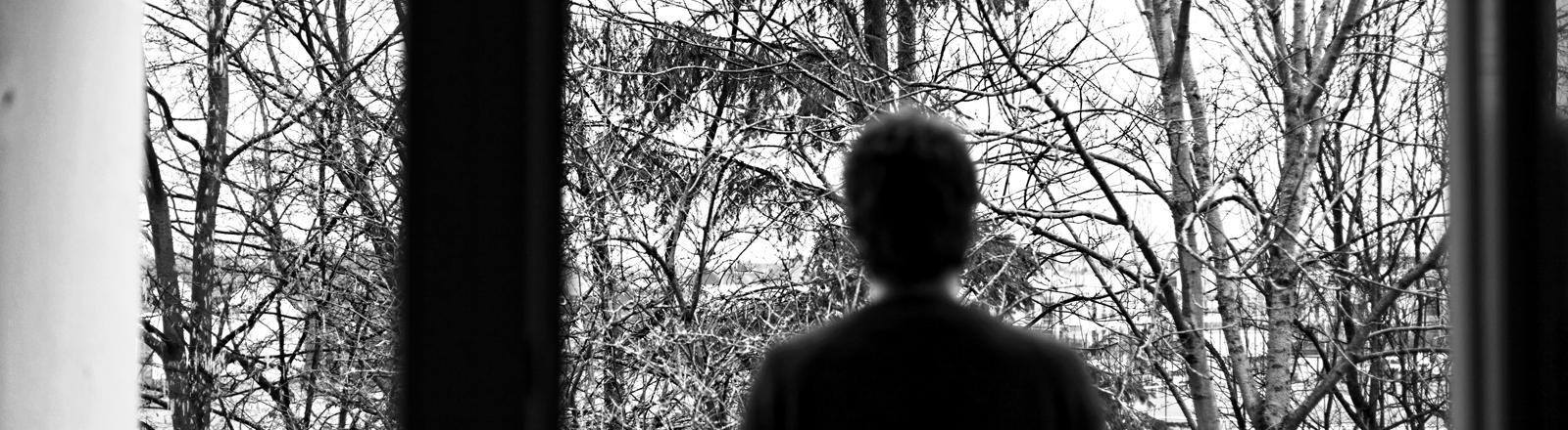 Mann steht vor einem Fenster und sieht nach draußen