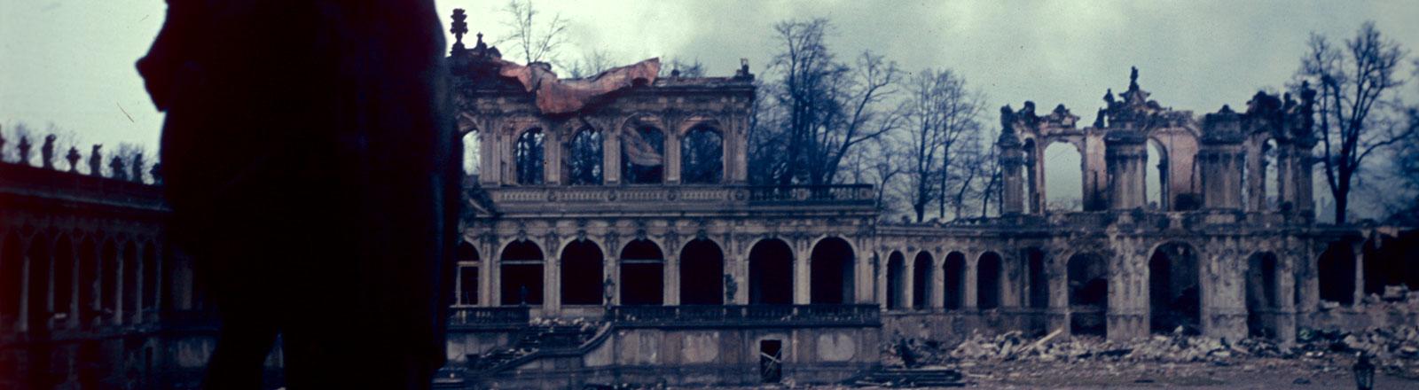 Nach den Luftangriffen der britischen und amerikanischen Alliierten auf Dresden vom 13. bis 15. Februar 1945 liegt der Dresdner Zwinger in Trümmern, im Hintergrund zeugen Rauchwolken von der noch brennenden Innenstadt.