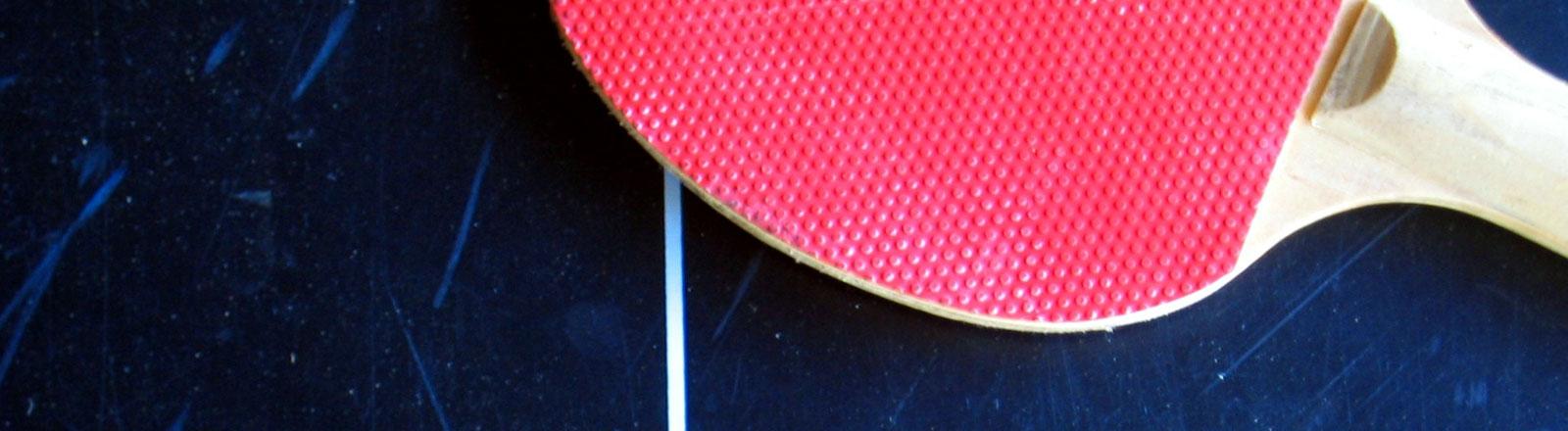 Ein Tischtennisschläger auf einer Tischtennisplatte.