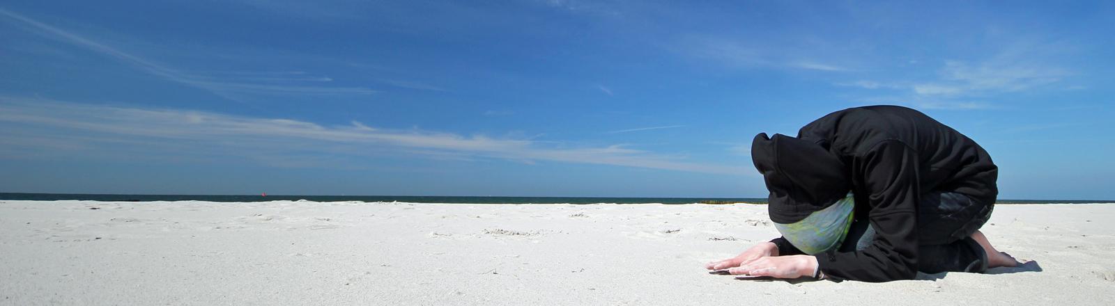 Ein Mann kniet im Sand und betet.