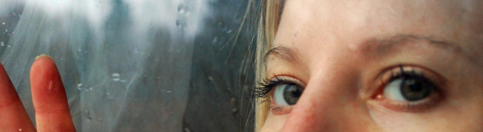 Eine Frau schaut an einem verregneten Tag durchs Fenster.