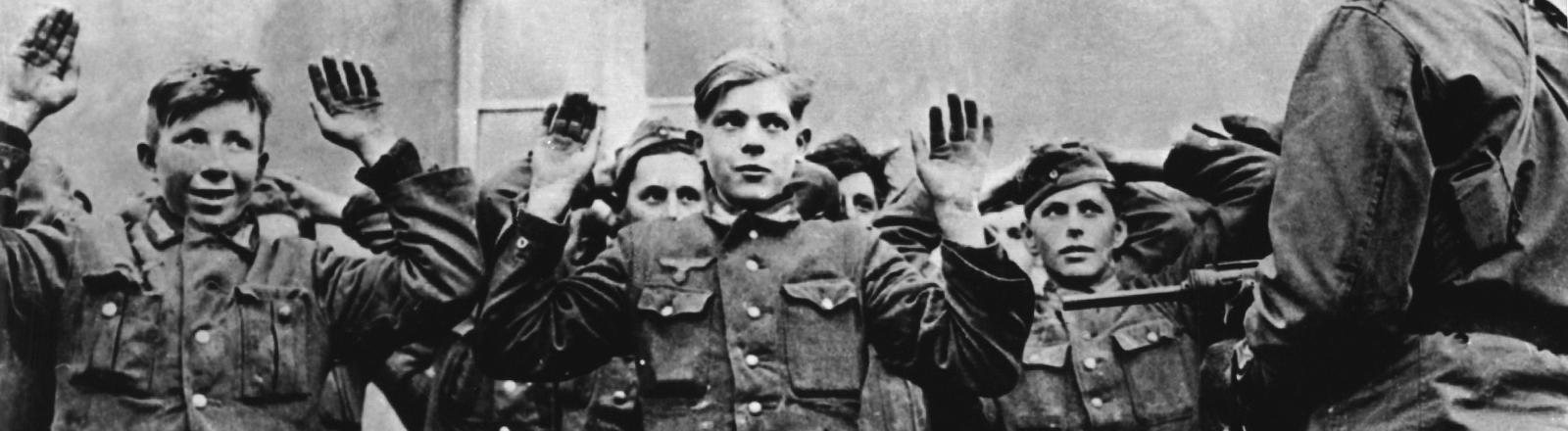 Mehrere junge, deutsche Soldaten werden von amerikanischen Truppen gefangen genommen.