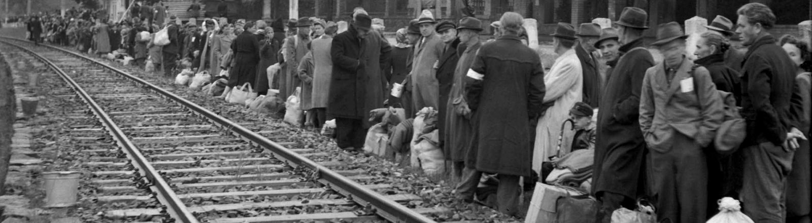 Deutsche Vertriebene stehen an einem Gleis und warten auf ihren Abtransport.