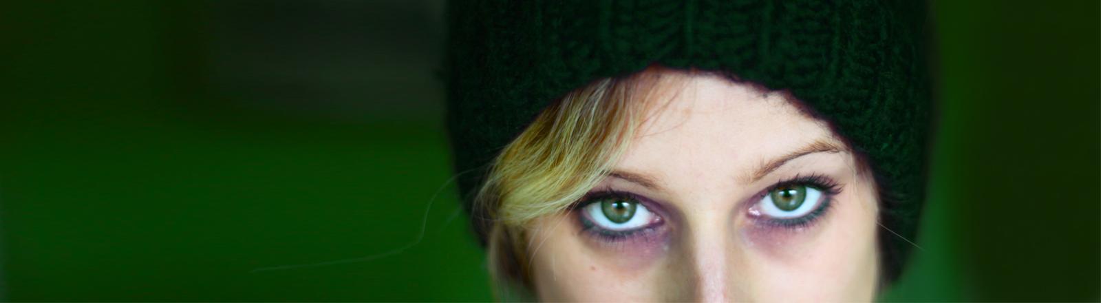 Eine Frau mit Mütze schaut verletzt-drohend in die Kamera.