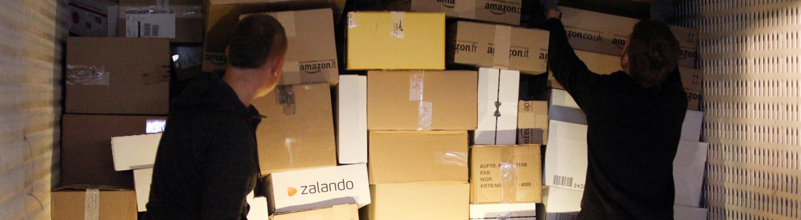 Paketzusteller laden Pakete und Päckchen in einen Transporter.