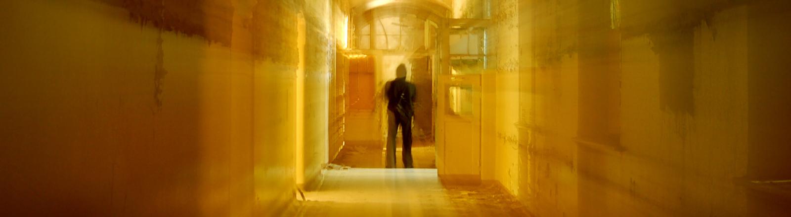 Ein Mann steht einsam in einem langen Flur.