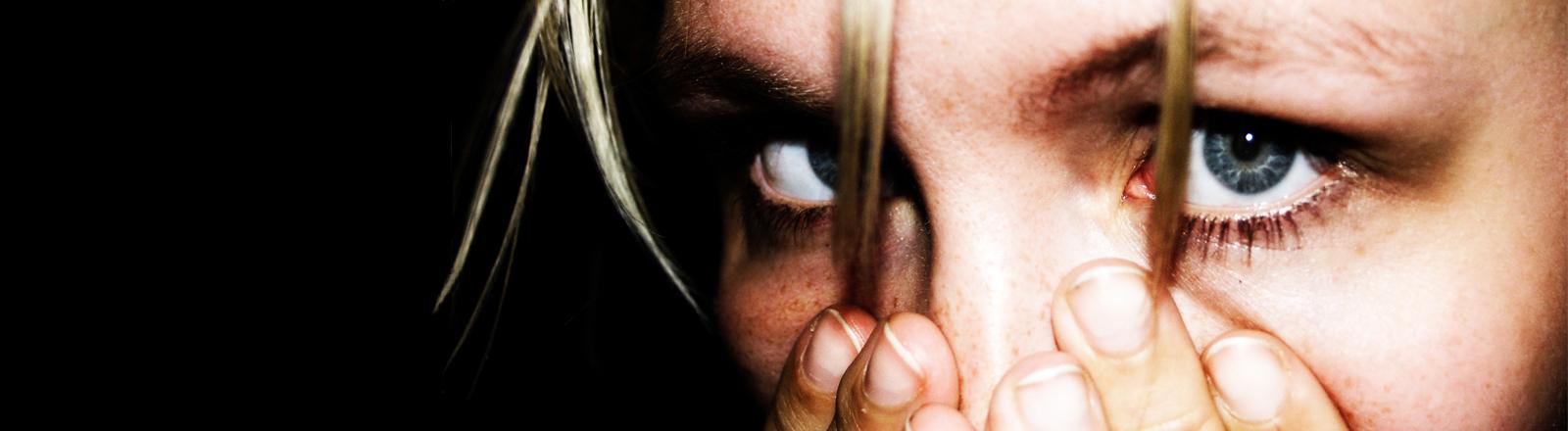 Eine Frau hält sich erschrocken die Hände vor den Mund und reißt die Augen auf.