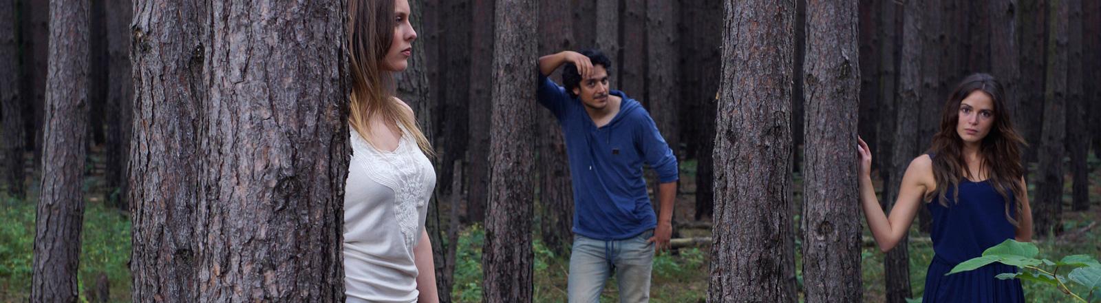 In einem Wald stehen zwei Frauen und ein Mann. Alle schauen in eine andere Richtung.