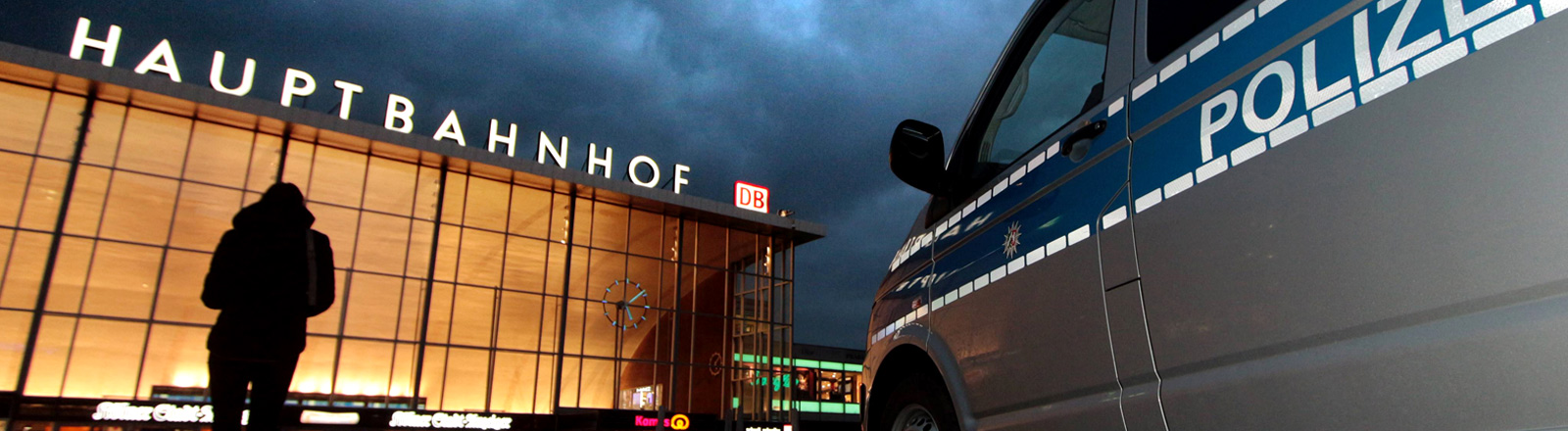 Eine junge Frau vor dem Kölner Hauptbahnhof, daneben ein Polizeiauto