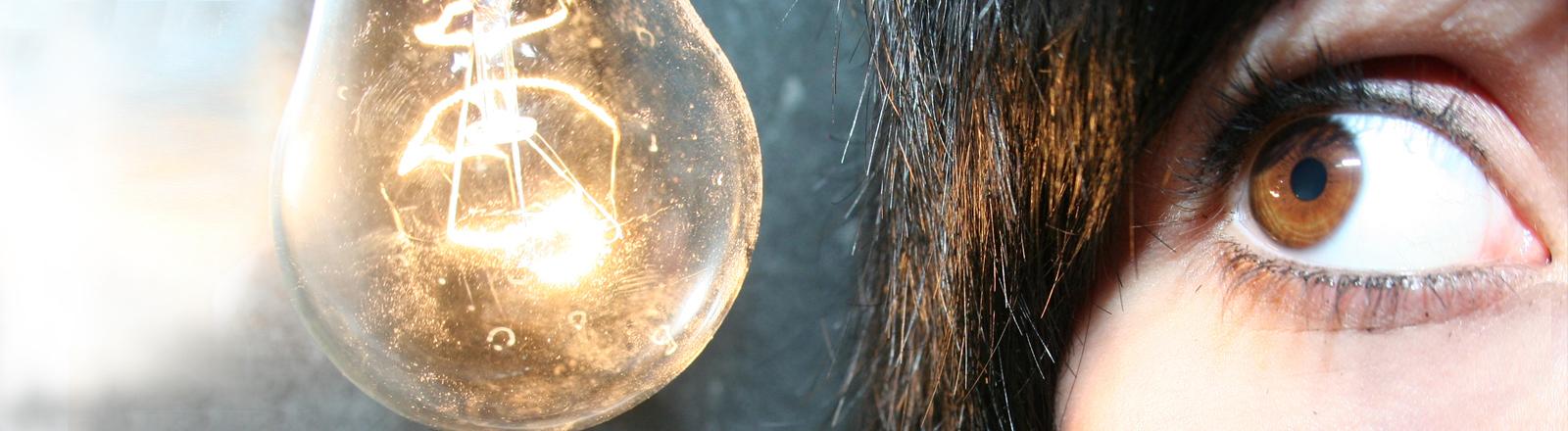 Eine Frau schaut ängstlich auf eine Glühbirne.