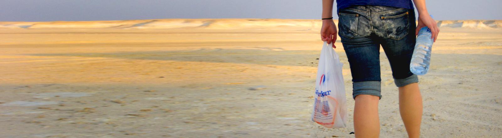 Eine Frau geht mit Lebensmitteln und Wasser in die Wüste.