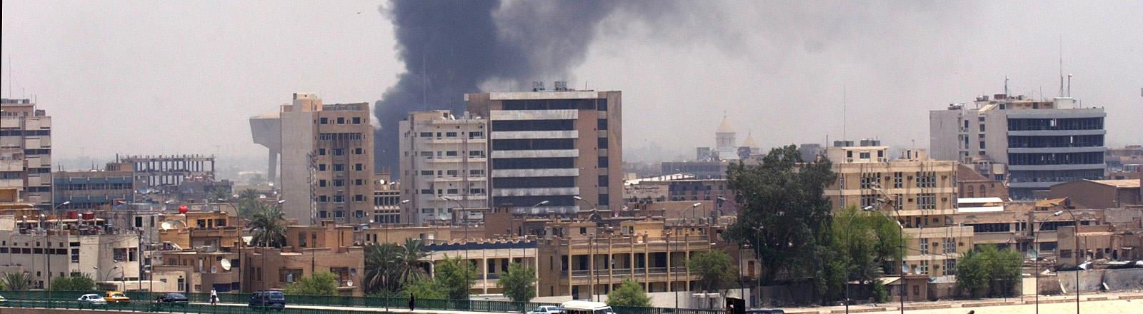 Stadtansicht von Bagdad, hinter Häusern steigt Rauch auf