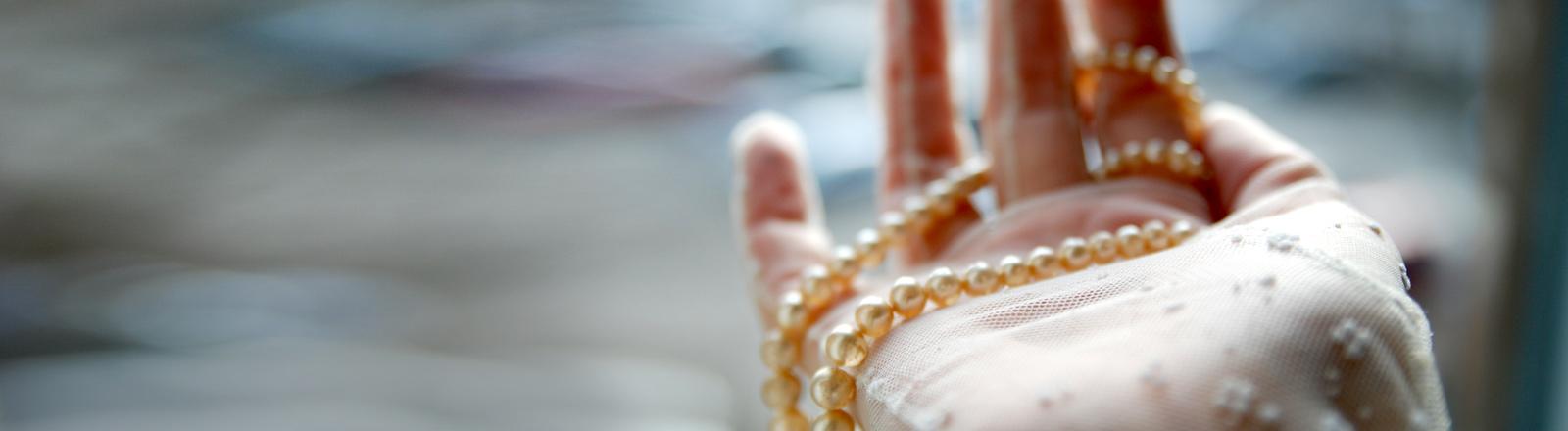 Eine Perlenkette in einer Hand.