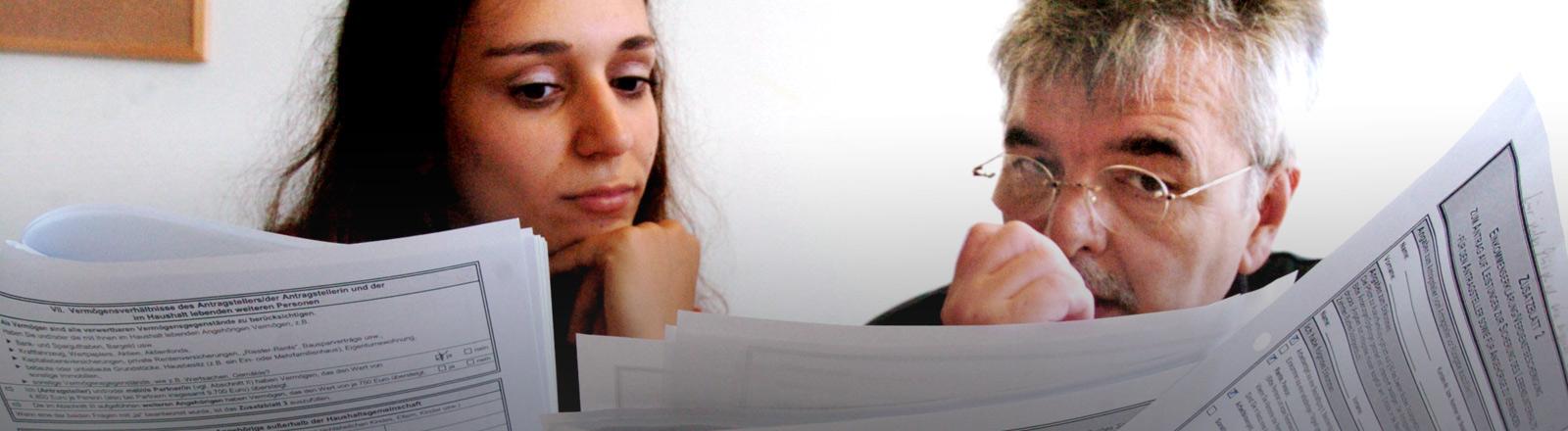 Frau und Mann lesen einen Hartz-IV-Antrag.