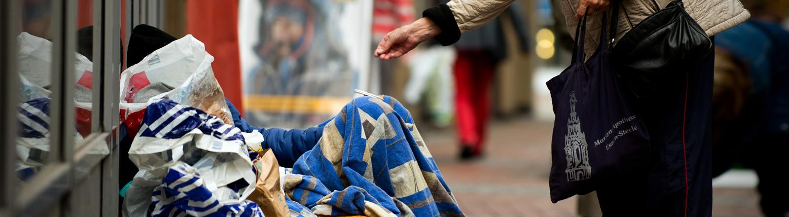Eine Person reicht einem Obdachlosen die Hand.