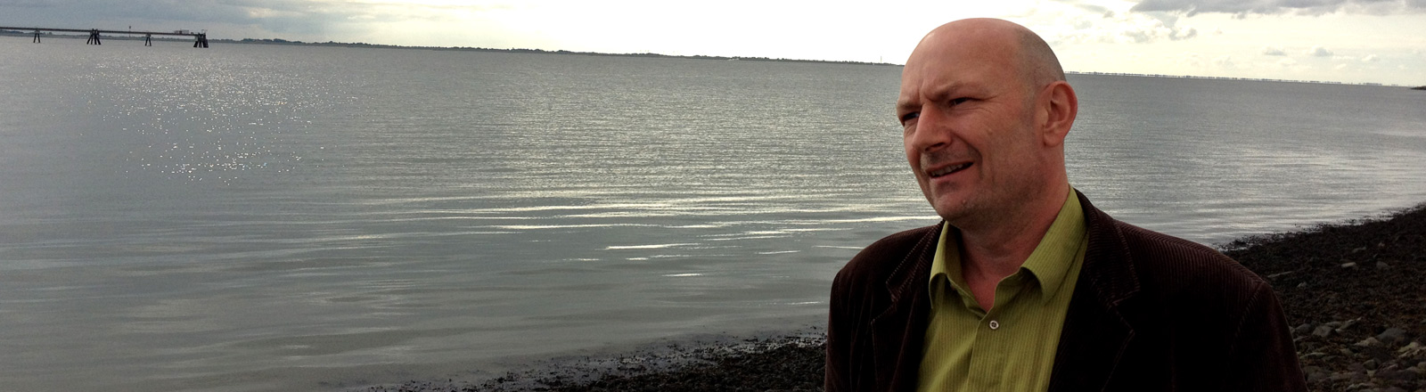 Künstler Ruppe Koselleck an einem Strand, wo er Rohöl sammelt.