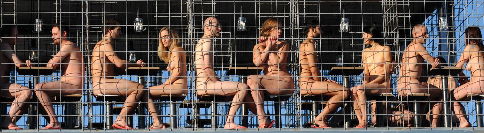 Nackte Menschen sitzen in einem großen Käfig.
