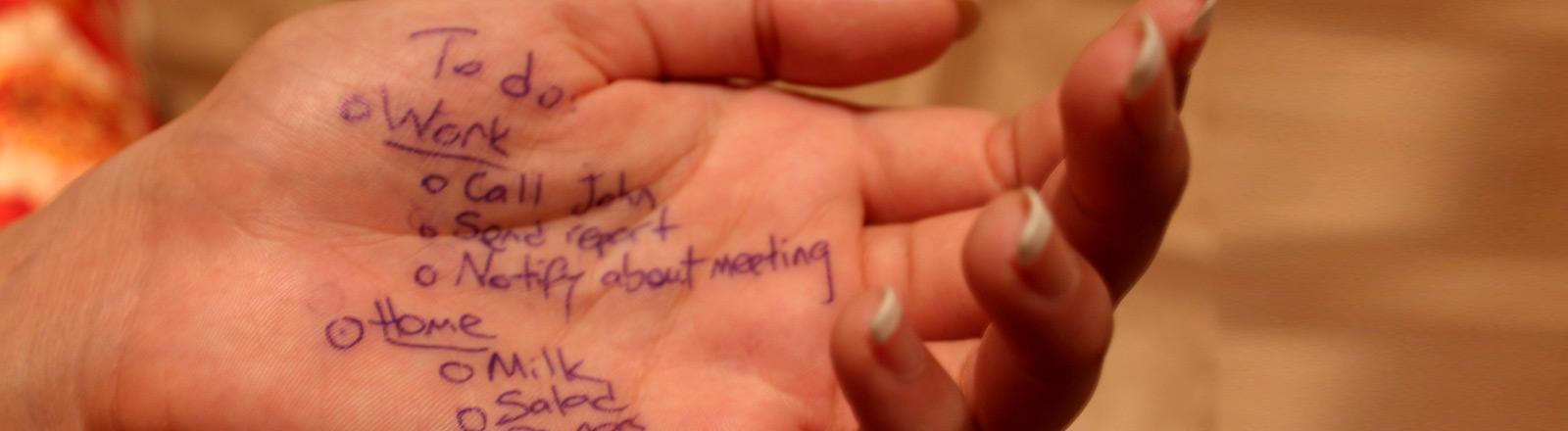 Eine Hand mit zwei Listen darauf geschrieben.