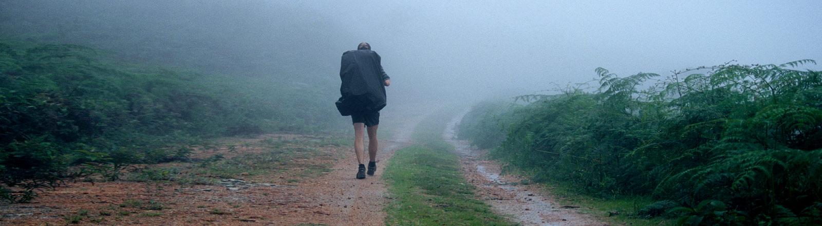 Ein Wanderer im Nebel mit Rucksack.