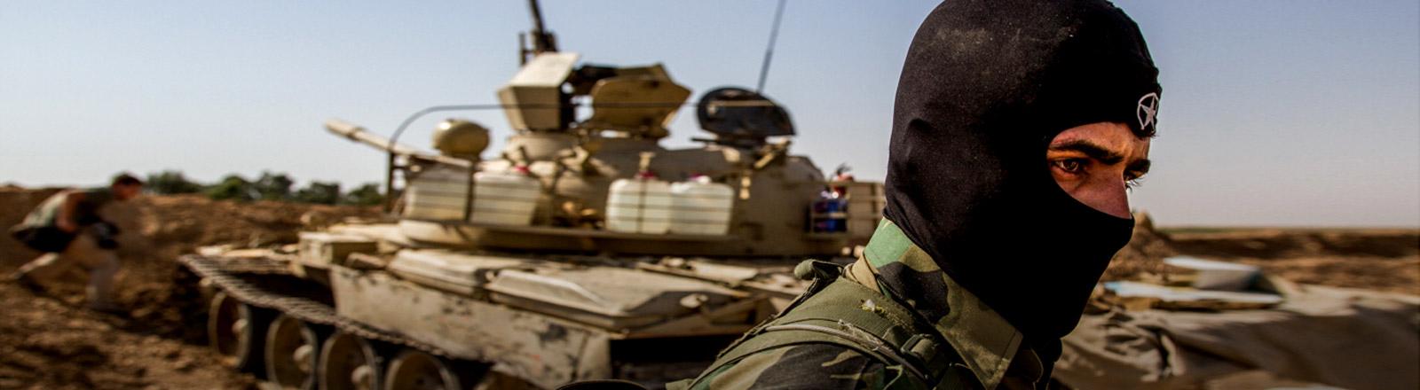 Ein kurdischer Soldat vor einem Panzer.
