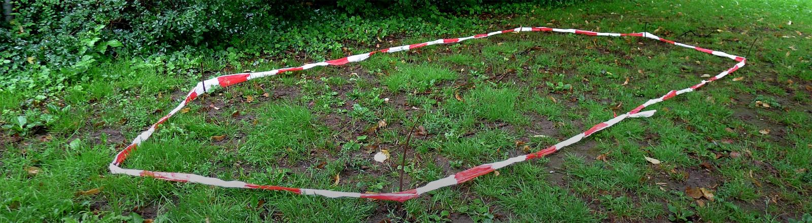 Auf einer Rasenfläche ist mit Absperrband die Position des verschwundenen Zeltes markiert