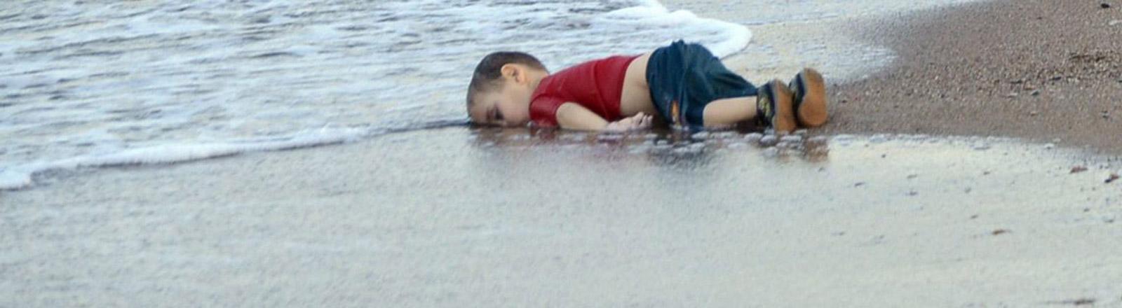 Ein dreijähriger Junge liegt tot am Strand.