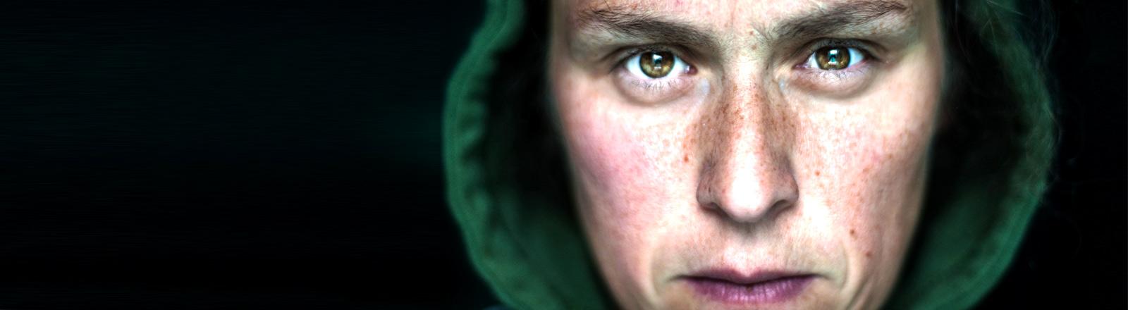 Eine Person im Hoodie mit entschlossenem Blick