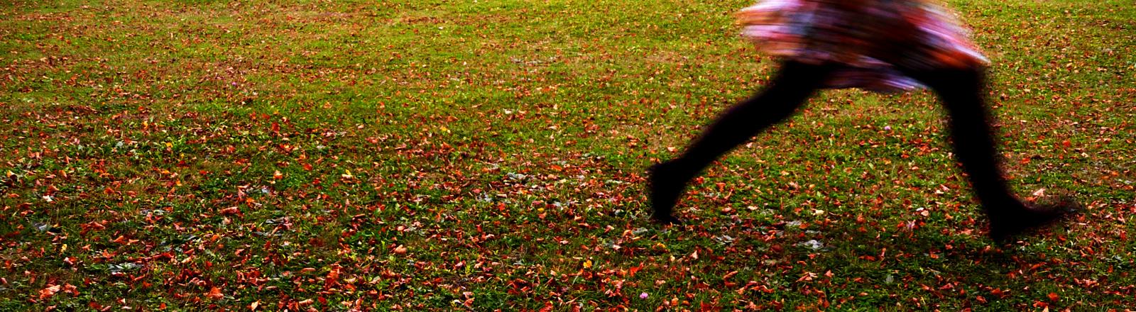 Eine Frau läuft in einer Herbstlandschaft davon