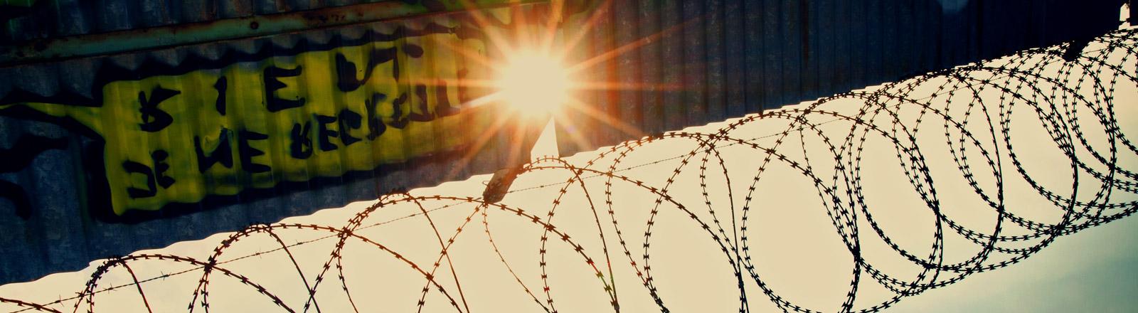 Die Sonne scheint zwischen einem Zaun hindurch.