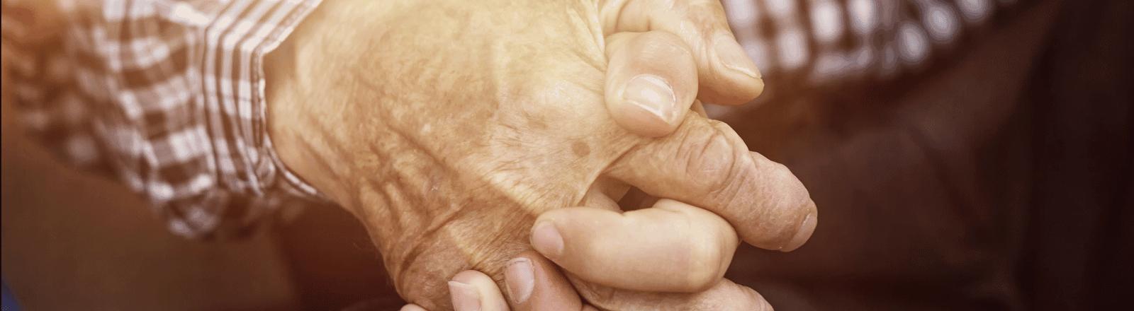 Frau hält die Hand eines alten Mannes