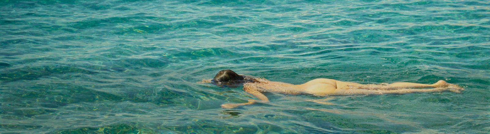 Eine nackte Frau schwimmt im Wasser.