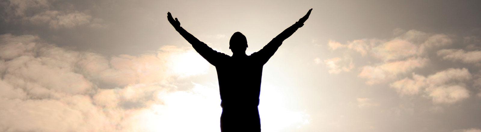 Ein Mann steht vor dem Himmel und breitet die Arme aus.